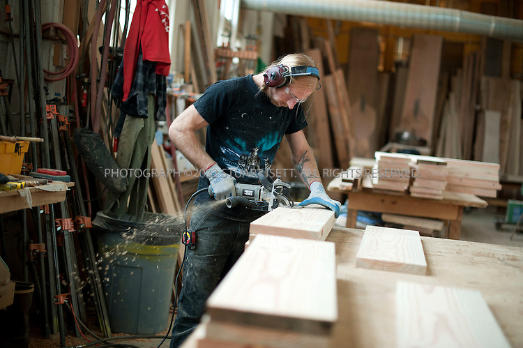 7/28/2010--Seattle, WA USA..Ron Nass, 28, works on building tables from reclaimed fir at Meyer Wells...Meyer Wells builds modern furniture from reclaimed urban trees in their facility in Seattle, WASH. Seth Meyer and John Wells started the company have successfully merged their environmental idealism with a business model that plays right into the Pacific Northwest's passion for sustainable forests. ..Meyer Wells harvests development-doomed or storm-damaged urban trees from Seattle neighborhoods and builds high-end custom furniture. The business is four years old and has grown every year in defiance of the recession; in 2009 they had $850,000 in gross sales. ..©2010 Stuart Isett. All rights reserved.