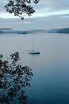 Boat moored near Orcas Island with fog rolling in over the water in the background