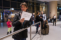 "Max Budovitch, of Somerville, Mass., holds a sign in Arabic reading ""My country is your country / So, welcome / Free legal services,"" outside the international arrivals area of Terminal E in Logan Airport in Boston, Massachusetts, USA, on Tues., Feb. 7, 2017. Budovitch was there volunteering as an Arabic-English translator for anyone needing free legal advice coordinated by the American Immigration Lawyers Association. The attorneys were there because of ongoing issues caused by an executive order signed by President Donald Trump banning travel to the US by people from seven Muslim-majority countries."