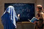 Marzia, who like many Afghans goes by only one name, teaches first grade to a group of girls and women at a school in a private residence in Kandahar, Afghanistan, Tuesday morning, April 20, 2009. Security concerns prompt the girls to wear burqas when outsiders visit. In hopes of increasing women's literacy, a joint Canadian International Development Agency and World Food Program initiative exchanges a monthly ration of food for each student's attendance in the class. Deteriorating security and a shortage of schools for girls have prompted hundreds of discreet schools to spring up in Kandahari homes.