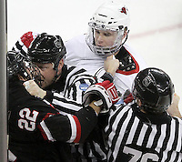 St. Cloud State's David Eddy is held back by Linesman Chad Evers as UNO's Ryan Walters looks on. UNO rallied from a 3-0 deficit to beat St. Cloud State 4-3 Saturday night at Qwest Center Omaha.  (Photo by Michelle Bishop)