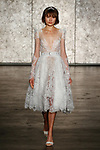 Model walks runway in a short crochet lace belted long sleeve ballerina, from Inbal Dror Fall 2018 bridal collection on October 5, 2017; during New York Bridal Fashion Week.