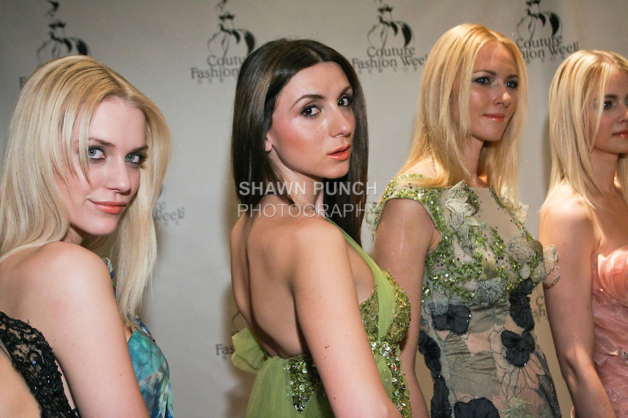 Models pose on red carpet after the Edward Arsouni fashion show, during Couture Fashion Week Fall 2011.