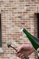 Herve Jestin, oenologist and chief winemaker holding a bottle of champagne Beuverie 1983 vintage that he will disgorge manually. After removing the capsule cork a little of the wine pours out of the bottle. This wine is then replaced by the liqueur d'expedition and the bottle is then recorked Champagne Duval Leroy, Vertus, Cotes des Blancs, Champagne, Marne, Ardennes, France