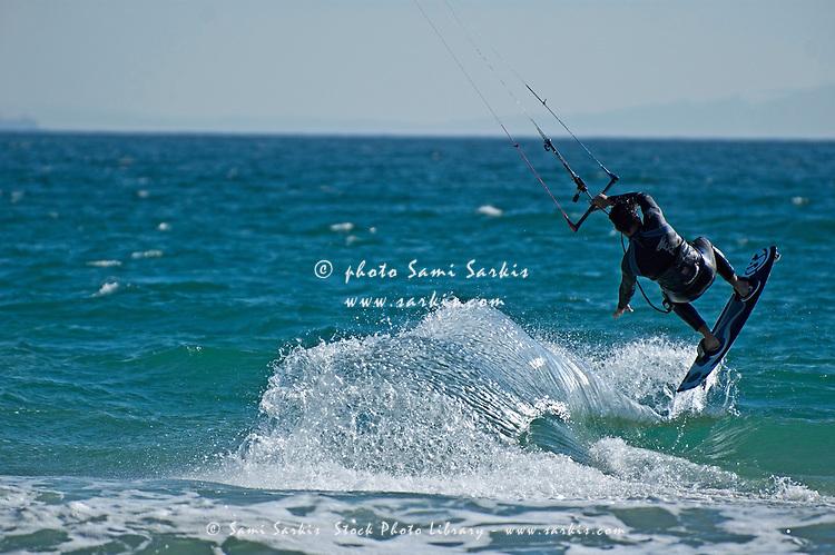 Kite surfer jumping over a wave, Playa de los Lances, Tarifa, Spain.
