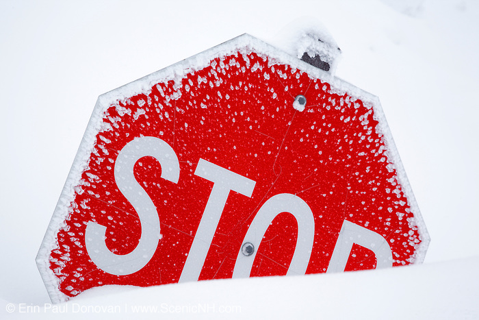 Stop sign sticking out of snow bank at C.L. Graham Wangan Grounds Scenic Overlook along the Kancamagus Highway (route 112), which is one of New England's scenic byways after a snow storm. Located in the White Mountains, New Hampshire USA