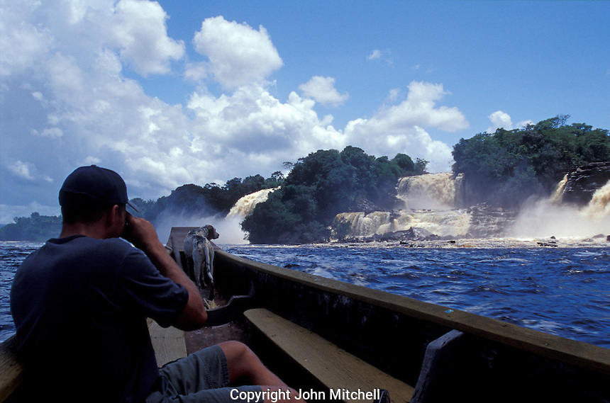 Tourist photographing Saltos Hacha from a boat on the Canaima Lagoon, Canaima National Park,  Bolivar State, Venezuela
