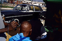 Barbershop haircut on a road in Diepkloof, Soweto, South Africa. South west of Johannesburg, Soweto is South Africa's largest township and was founded around 100 years ago to provide housing for black people. The estimated population is 2 to 3 million. (Photo by: Per-Anders Pettersson)