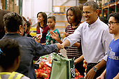 """(2nd R-L) United States President Barack Obama, first lady Michelle Obama, and their daughters Sasha Obama, 12, and Malia Obama, 15, help pack and sistribute bags of food to needy children and seniors at the Capital Area Food Bank November 27, 2013 in Washington, DC. According to the White House, the first family was joined by family and friends and members of The Mission Continues, """"an organization of post-9/11 veterans who are awarded community service fellowships.""""  <br /> Credit: Chip Somodevilla / Pool via CNP"""