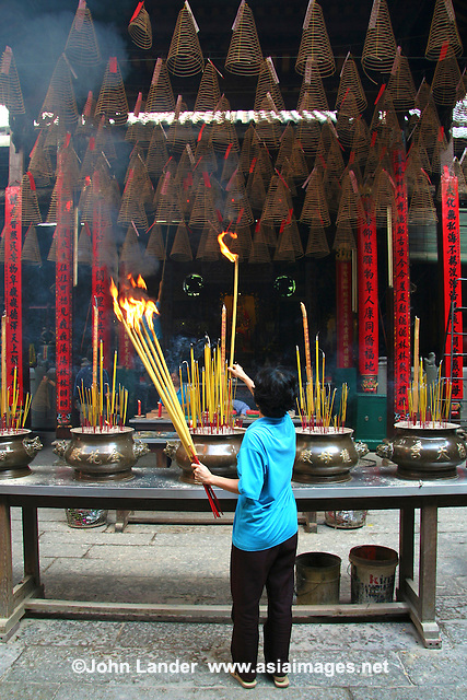Lighting Spiral Incense Coils at Thien Hau Pagoda -  Spiral incense is preferred by many Vietnamese and Chinese for its long-lasting burning power. There are many forms of  incense and its use and formulation is strongly tied to traditional medicine. The use of incense has long been as much for health and well-being as religious purposes.