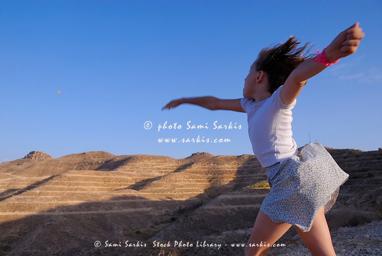 Girl (6-7) throwing stone in sky, Tunisia, Matmata