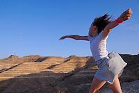 Girl (6-7) throwing stone in sky, Tunisia, Matmata