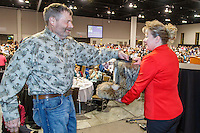 Musher Jim Lanier draws his starting position from a mukluk held by Anchorage Chrysler Dodge sponsor representative Kristine Horst at the 2016 Iditarod musher position drawing banquet at the Dena'ina convention center in Anchorage, Alaska on Thursday March 3, 2016  <br /> <br /> &copy; Jeff Schultz/SchultzPhoto.com ALL RIGHTS RESERVED<br /> DO NOT REPRODUCE WITHOUT PERMISSION