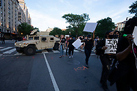 Protestors walk past a military vehicle in Washington, D.C., U.S., on Monday, June 1, 2020, following the death of an unarmed black man at the hands of Minnesota police on May 25, 2020.  More than 200 active duty military police were deployed to Washington D.C. following three days of protests.  Credit: Stefani Reynolds / CNP/AdMedia