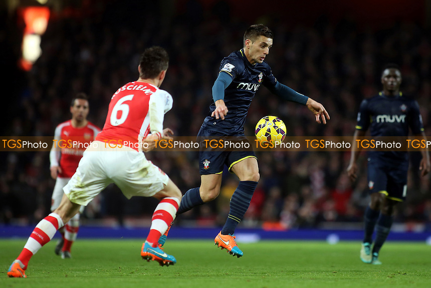 Dusan Tadic of Southampton takes on the Arsenal defence - Arsenal vs Southampton - Barclays Premier League Football at the Emirates Stadium, London - 03/12/14 - MANDATORY CREDIT: Paul Dennis/TGSPHOTO - Self billing applies where appropriate - contact@tgsphoto.co.uk - NO UNPAID USE