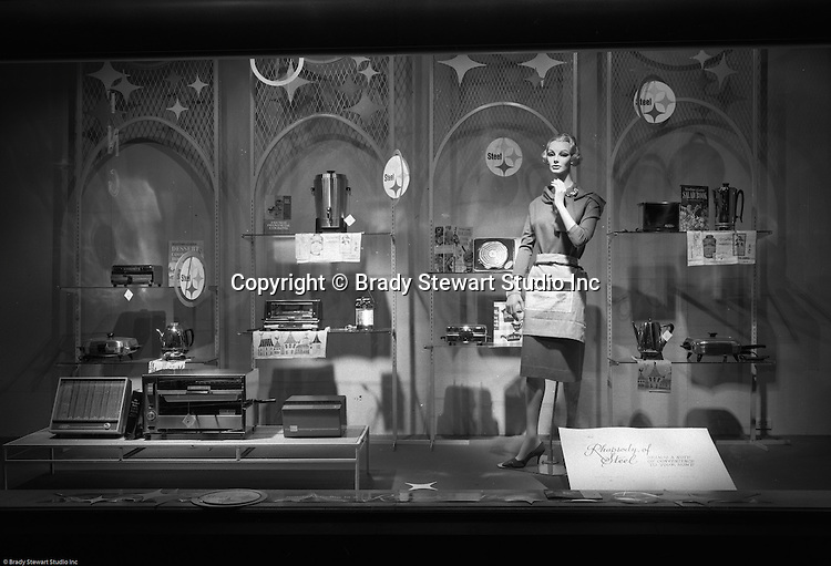 Pittsburgh PA: View of Christmas window display at Horne's department store in downtown Pittsburgh. Woman manikin dressed up for kitchen duty and surrounded by steel appliances for the home.  The display was part of the Rhapsody of Steel promotion at Horne's.  US Steel launched an awareness campaign of all the current uses of steel in everyday products.  During this time, ALCOA Aluminum Company of America also headquartered in Pittsburgh, was aggressively competing to enter markets where US  steel companies traditional dominated market share. Examples included beer and food Cans, appliances, automobile parts, children toys / bicycles, and more.