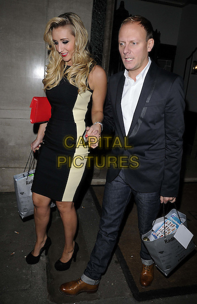 Catherine Tyldesley & Antony Cotton.The Radio Times Covers Party, Claridges hotel, Brook St., London, England..January 17th, 2012.full length dress cream panel side red clutch bag holding hands jeans denim black suit goody bag.CAP/CAN.©Can Nguyen/Capital Pictures.