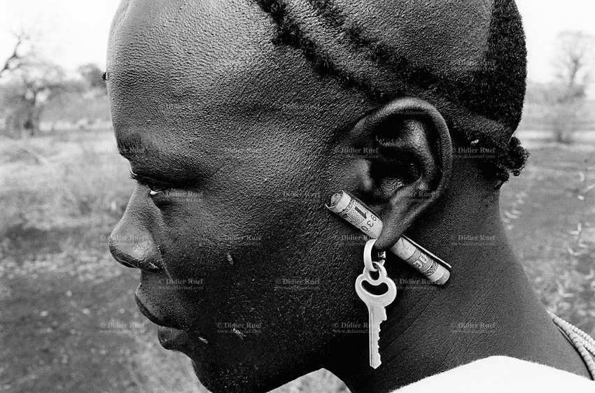 Ethiopia. South Omo Zone. Salamago district. Hana (little village). Bodi tribe. Nomadic. Young man wearing a key as earring and a rolled ethiopian banknote of one bir in a hole through his ear's lobe. The Bodi tribe is located in the Debub Omo Zone (South Omo Zone) of the Southern Nations, Nationalities and Peoples's région. © 2001 Didier Ruef
