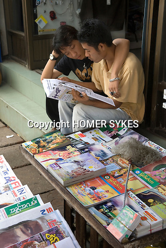 Street vendor selling magazines with friend. Yangon Rangoon Myanmar Burma 2006.
