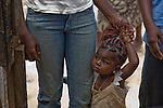 A child in the Agboyi-Ketu section of Lagos, Nigeria, holds her mother's hand.