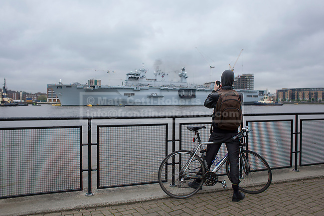 04/05/2012. LONDON, UK. A member of the public uses his phone to take a picture of HMS Ocean, the Royal Navy's helicopter carrier, after she made her way up the Thames to moor in Greenwich, London, today (04/05/12). HMS Ocean has been deployed as part of an exercise involving the RAF, British Army and Royal Navy taking place across London as part of security preparations for the 2012 London Olympic Games. Photo credit: Matt Cetti-Roberts