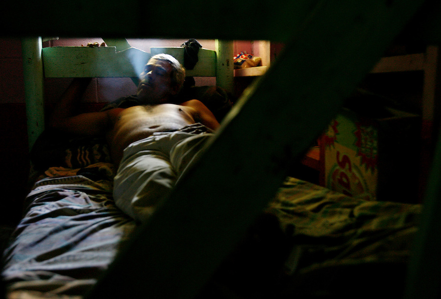 Mecca for Misery.Leonardo Lopez Armenta, 49, smokes a cigarette on his bunk bed. He shares the 200 square foot room with seven men at $35 per person/per week to stay in an illegal residence in Mecca. He says it is better than sleeping in the streets.
