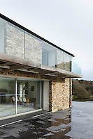 An existing side extension was demolished to allow for a new balcony with a glass balustrade off the master bedroom, echoed by large sliding glass doors opening from the kitchen/dining area below