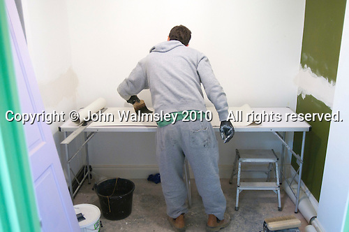 Painting & Decorating student applying paste to some lining paper, Able Skills, Dartford, Kent.