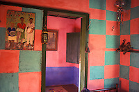 Interior of a brazilian rural house, colorful walls, Lavrinha, Minas Gerais, Brazil. Popular culture. Painting portraying rural workers. Door and kerosene lamp