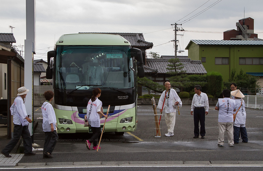 Pilgrims, known as a Henro, board a bus to take them to the next temple on the Shikoku 88 Temple pilgrimage, Matsuyama, Eihime, Japan.. Friday, June 26th 2015