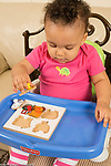 12 month old baby girl at home using pincer grasp to pick up peg puzzle piece