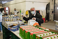 """Auswirkungen der Corona-Krise.<br /> Die Corona-Situation hat auch fuer die Hilfsorganisation """"Berliner Tafel"""" weitreichende Konsequenzen. 42 LAIB und SEELE-Ausgabestellen mussten schliessen, nur drei der Ausgabestellen haben noch geoeffnet. Rund 50.000 beduerftige Menschen kommen ueblicherweise jeden Monat an den Ausgabestellen. Damit die Menschen weiterhin gespendete Lebensmittel erhalten koennen, beliefert die Berliner Tafel nun die Menschen zu Hause. In einer Halle auf dem Berliner Grossmarkt packen freiwillige Helferinnen und Helfer Tueten mit Lebensmitteln, die verteilt werden. In einigen Bezirken uebernehmen Radfahrerinnen und Radfahrer der """"Rebel Riders"""" mit Lastenraedern die Vor-Ort-Verteilung von Tuer zu Tuer.<br /> LAIB und SEELE ist eine Aktion der Berliner Tafel e.V., der Kirchen und des Rundfunk Berlin Brandenburg, rbb.<br /> Im Bild: Der Berliner Erzbischof Heiner Koch (rechts im Bild) besuchte am Montag den 30. Maerz 2020 die """"Berliner Tafel"""" und half auch beim packen und verladen der Lebensmitteltueten.<br /> 30.3.2020, Berlin<br /> Copyright: Christian-Ditsch.de<br /> [NUR FUER REDAKTIONELLE ZWECKE! Werbung nur auf Anfrage beim Fotografen. Inhaltsveraendernde Manipulation des Fotos nur nach ausdruecklicher Genehmigung des Fotografen. Vereinbarungen ueber Abtretung von Persoenlichkeitsrechten/Model Release der abgebildeten Person/Personen liegen nicht vor. NO MODEL RELEASE! Don't publish without copyright Christian-Ditsch.de, Veroeffentlichung nur mit Fotografennennung, sowie gegen Honorar, MwSt. und Beleg. Konto: I N G - D i B a, IBAN DE58500105175400192269, BIC INGDDEFFXXX, Kontakt: post@christian-ditsch.de<br /> Bei der Bearbeitung der Dateiinformationen darf die Urheberkennzeichnung in den EXIF- und  IPTC-Daten nicht entfernt werden, diese sind in digitalen Medien nach §95c UrhG rechtlich geschuetzt. Der Urhebervermerk wird gemaess §13 UrhG verlangt.]"""