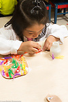 Education preschool 3 year olds girl applying glue to object for collage with feathers art activity