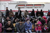Pictured: Migrants rest on the ground Monday 22 February 2016<br /> Re: Thousands of migrants, most from Syria, have landed to the port of Pireaus, after crossing the border from Turkey to various islands like Lesvos and Kos in Greece.