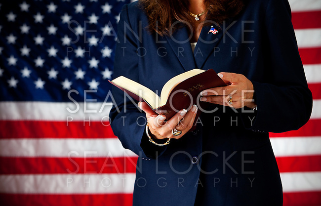 Series with an adult female in a suit, playing the part of a United States politician.  Different props provide a variety of concepts.  Standing in front of a US flag background.