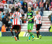 Jonjo Shelvey of Swansea City (right) shakes hands with Yann M'Vila of Sunderland after the final whistle during the Barclays Premier League match between Sunderland and Swansea City played at Stadium of Light, Sunderland