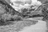 This black and white Colorado image was taken in the morning at the Maroon Bells Wilderness Area. The drive from Highway 82 near Aspen to the Maroon Bells Wilderness Area is a beautiful, winding 8 mile road that passes through Aspen trees, meadowns, and follows Maroon Creek. After you park in the lot, you'll find yourself walking this path as the iconic Maroon Bells appear before you. Possibly the most photographed mountains and landscape in Colorado, these two 14,000 feet mountains rise above Maroon Lake, and 2.3 miles further, Crater Lake.