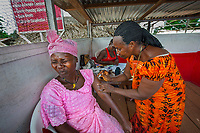 """Theresa, Doctor, Gbarnga, Liberia, 2014<br /> Patience receives her three-month Depo-Provera contraceptive shot from Theresa Gloli, a trained midwife and nurse in Liberia. Theresa manages a family planning health clinic that she sets up in the middle of the market in Gbarnga every Friday, knowing that it's the busiest day of the week for women to shop. In The Moment of Lift, Melinda Gates writes, """"When women are able to time and space their pregnancies, they're more likely to advance their education, earn an income, raise healthy children, and have the time and money to give each child the food, care, and education to thrive.... In fact, no country in the last fifty years has emerged from poverty without expanding access to contraceptives.... Contraceptives are the greatest life-saving, poverty-ending, women-empowering innovation ever created."""""""