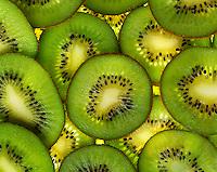 Agriculture - Overlapping backlit kiwi slices, studio.