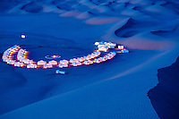 The semi-circular formation of the Ubari Magic Lodge tents are lit up against the desert night