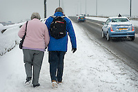 A couple walk over the bridge after an  early winter snow fall.