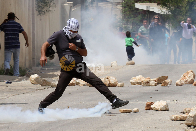 A Palestinian protester kicks back a tear gas canister fired by Israeli security forces during clashes following a protest Palestinian Prisoner's Day and against the expropriation of Palestinian land by Israel in the West Bank village of Kafr Qaddum, near the northern city of Nablus, April 17, 2015. The current number of Palestinians held in Israeli prisons is at least 6,200 and is the biggest for at least five years, according to figures from rights groups. Photo by Nedal Eshtayah