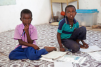 Jambiani, Zanzibar, Tanzania.  Primary School Boys and their Workbooks.  Students sit on the floor since the school has no furniture.