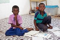 Jambiani, Zanzibar, Tanzania.  Primary School Boys and their Workbooks.  Students sit on the floor since the school has no furniture.