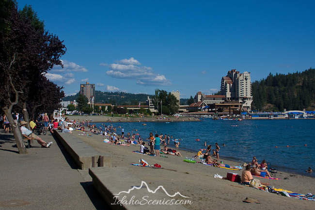 The city beach filled with swimmers and sunbathers on a hot summer day. The 5 star Coeur D Alene Resort dominates the downtown waterfront in this tourist destination of North Idaho.