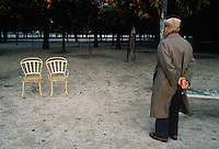 Elderly man standing in park looking at two empty chairs.
