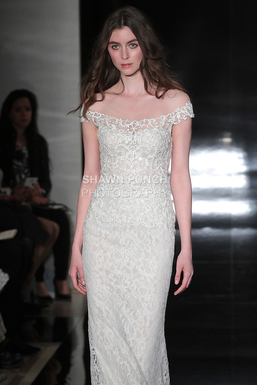 Model walks runway in an off-shoulder Chantilly lace gown with embroidered bodice, ruched back train, and laced up back, from the Reem Acra Spring 2017 bridal collection, during New York Bridal Fashion Week Spring Summer 2017, on April 15, 2016.