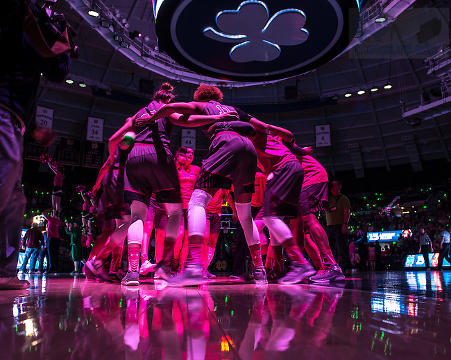 Feb. 14, 2016; The Women's Basketball team huddles under a pink spotlight at the annual Pink Zone game to raise funds and awareness for breast cancer research. (Photo by Matt Cashore/University of Notre Dame)