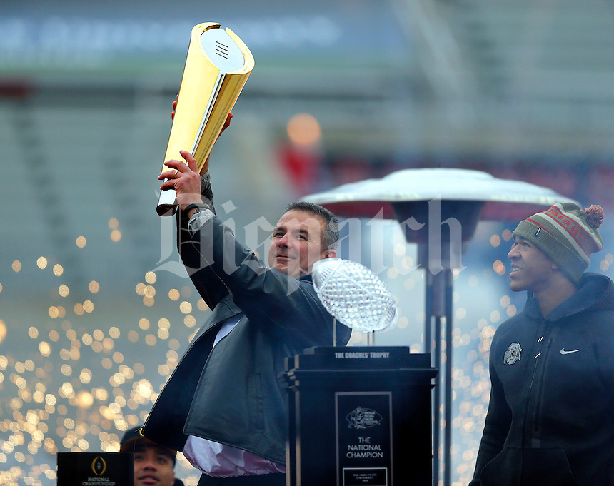 Head coach Urban Meyer holds the national championship trophy while wide receiver Evan Spencer watches during the Ohio State football National Championship celebration at Ohio Stadium on Saturday, January 24, 2015. (Columbus Dispatch photo by Jonathan Quilter)