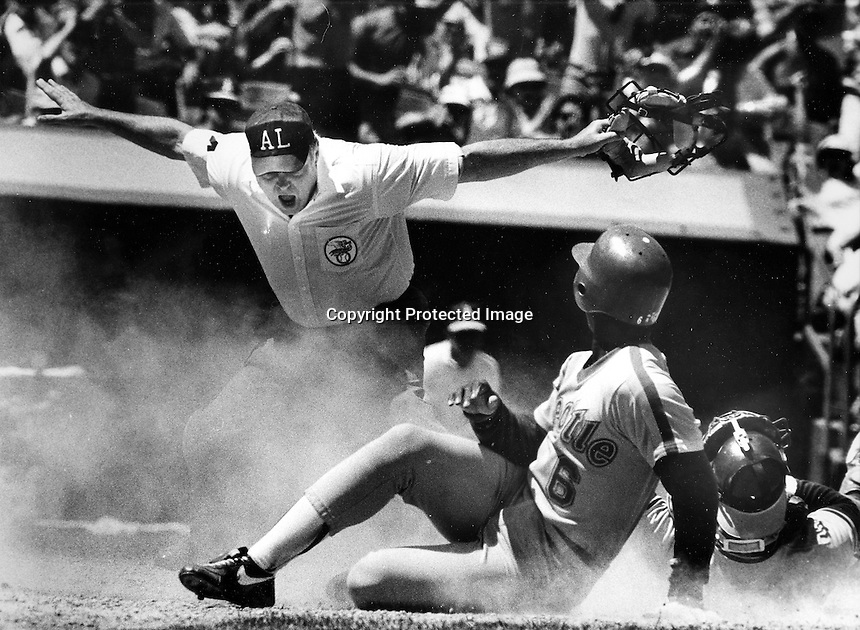 Umpire Marty Springstead gives the safe sign as Seattle Mariner's Darnell Coles slides, Oakland A's catcher Mike Heath on the ground. (photo 1984 by Ron Riesterer)